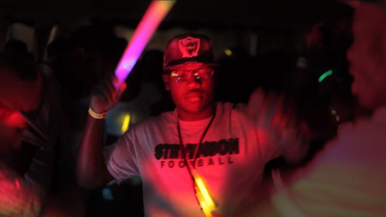 A raver dances and waves his light stick