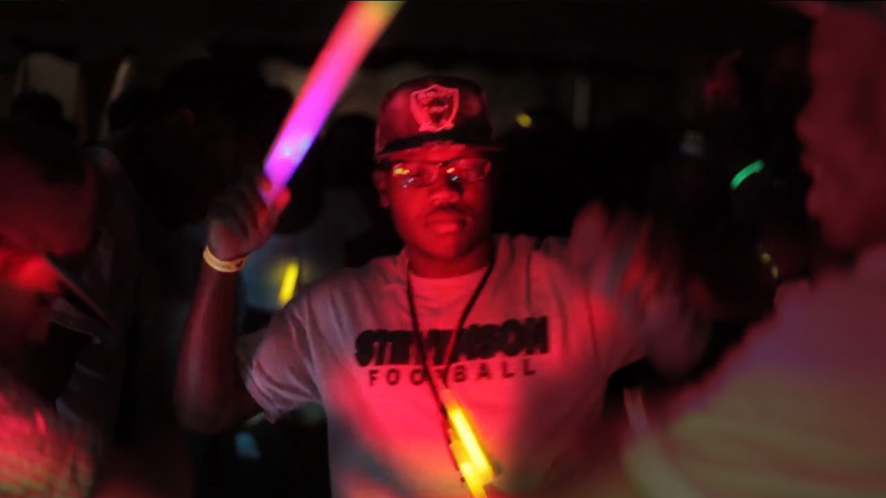 A raver dances and waves his light stick
